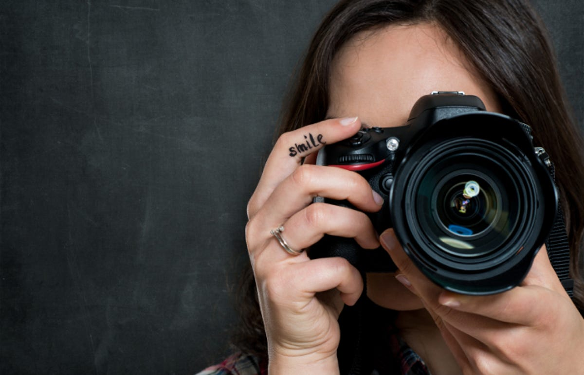 woman taking a picture with a DSLR camera