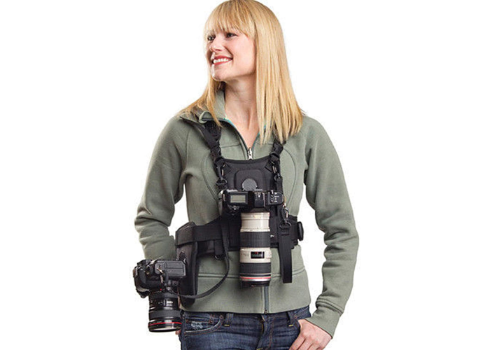 blonde woman wearing a black harness holding a camera