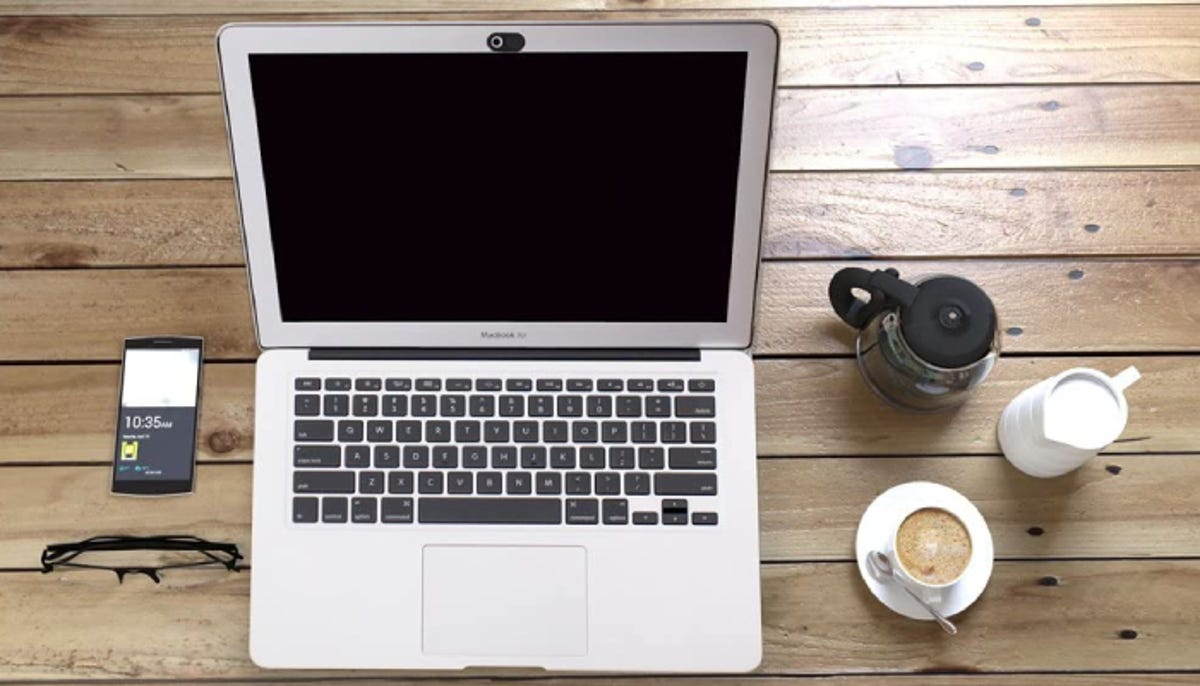 silver laptop with a black camera cover, sitting a wooden plank table next to glasses, a smartphone, and coffee cups