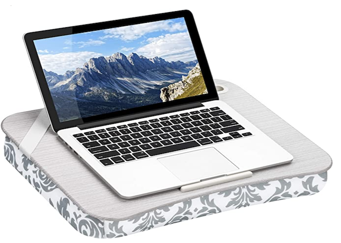 open laptop perched on a gray lap desk with a white and gray patterned cushion