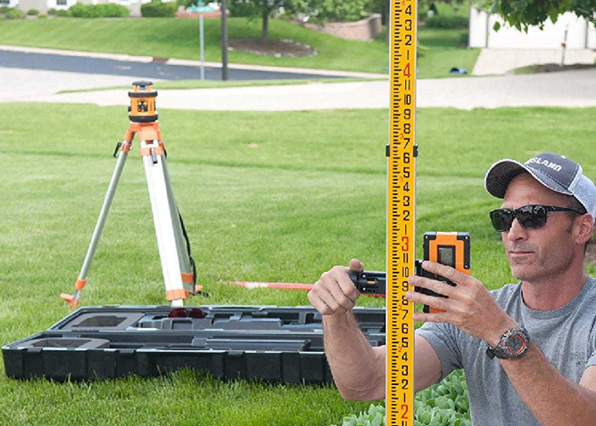 man measuring out the right level for an outdoor project with a laser tripod on the lawn behind him