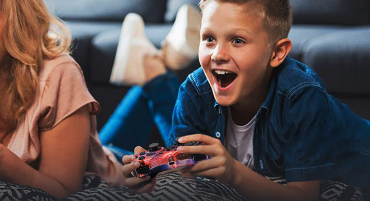 young boy holding a PS3 controller and smiling at the TV
