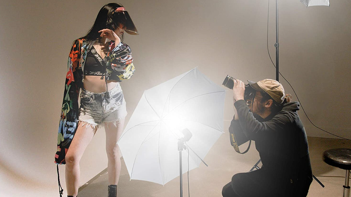 man in a photography studio shooting a photo of a woman lit up by a photo umbrella