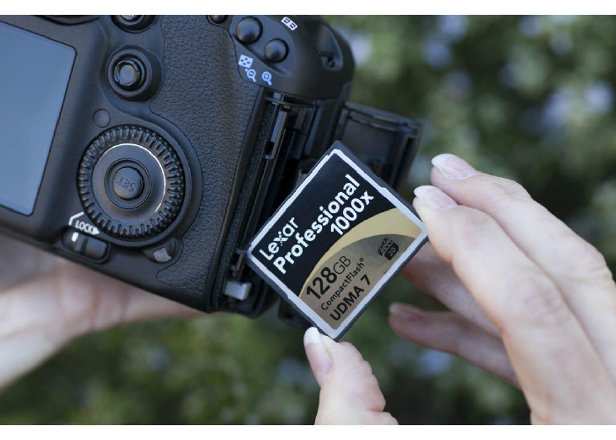 someone inserting a compactflash card into a black digital camera