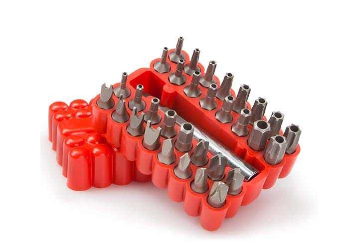lidless red plastic box with slots full of security drill bits