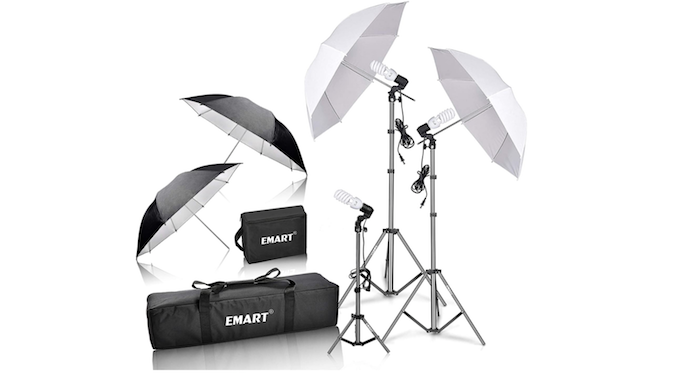 two black and two white photo umbrellas with two black carrying cases and a smaller umbrella-less light