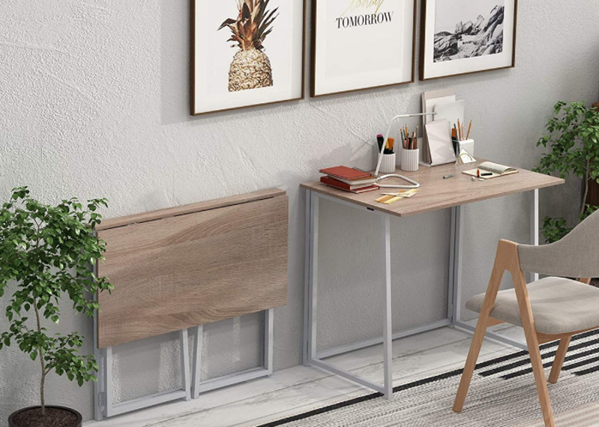 a collapsible desk with a wooden top set up in an office that's decorated with netural pictures and plants