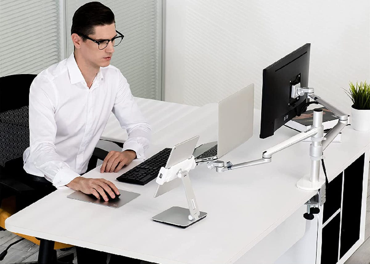 a man sitting at a desk with two monitors set up on a special stand