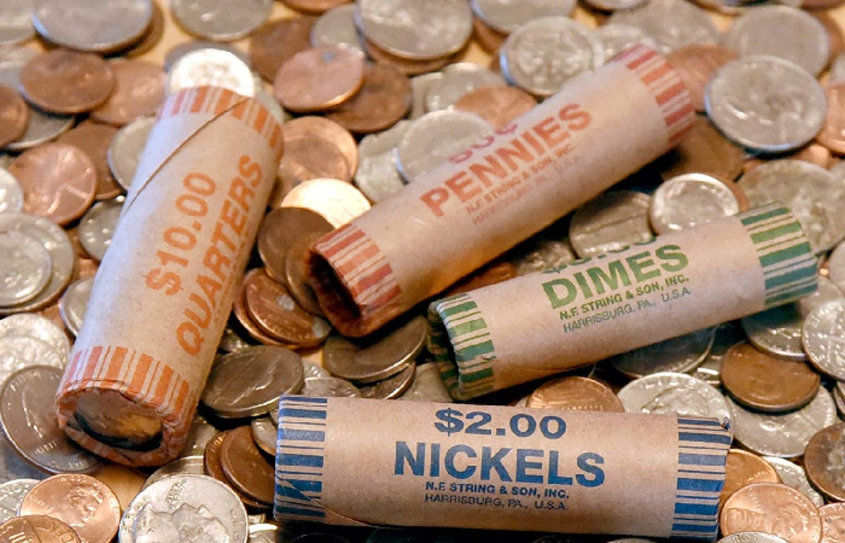 four coin wrappers lying on a bed of change