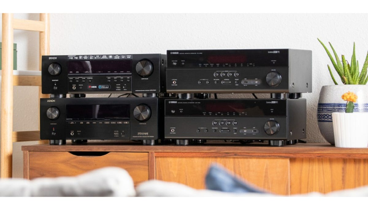 four stacked black stereo receivers on top of wooden drawers beside two plants