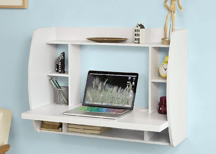 floating compartmentalized white wall desk holding a laptop and several other items and decorations