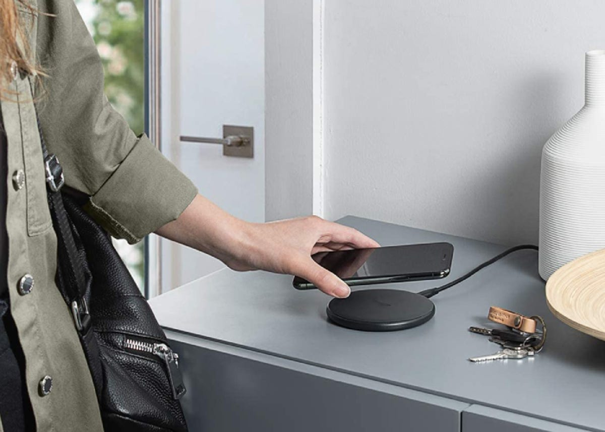 woman placing her iPhone on a wireless charger in the entry way of her home