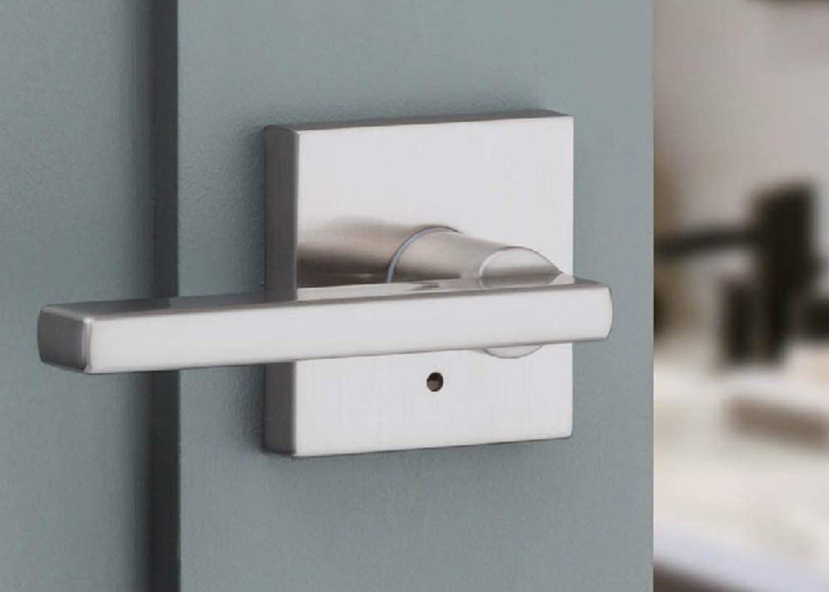closeup of a square cornered chrome door handle on a blue-gray door