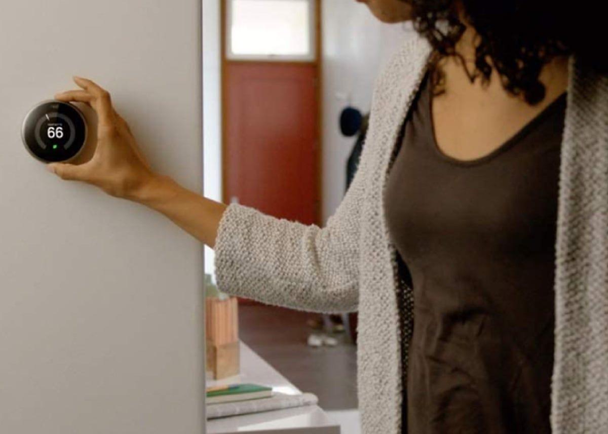 woman adjusting a round black smart thermostat