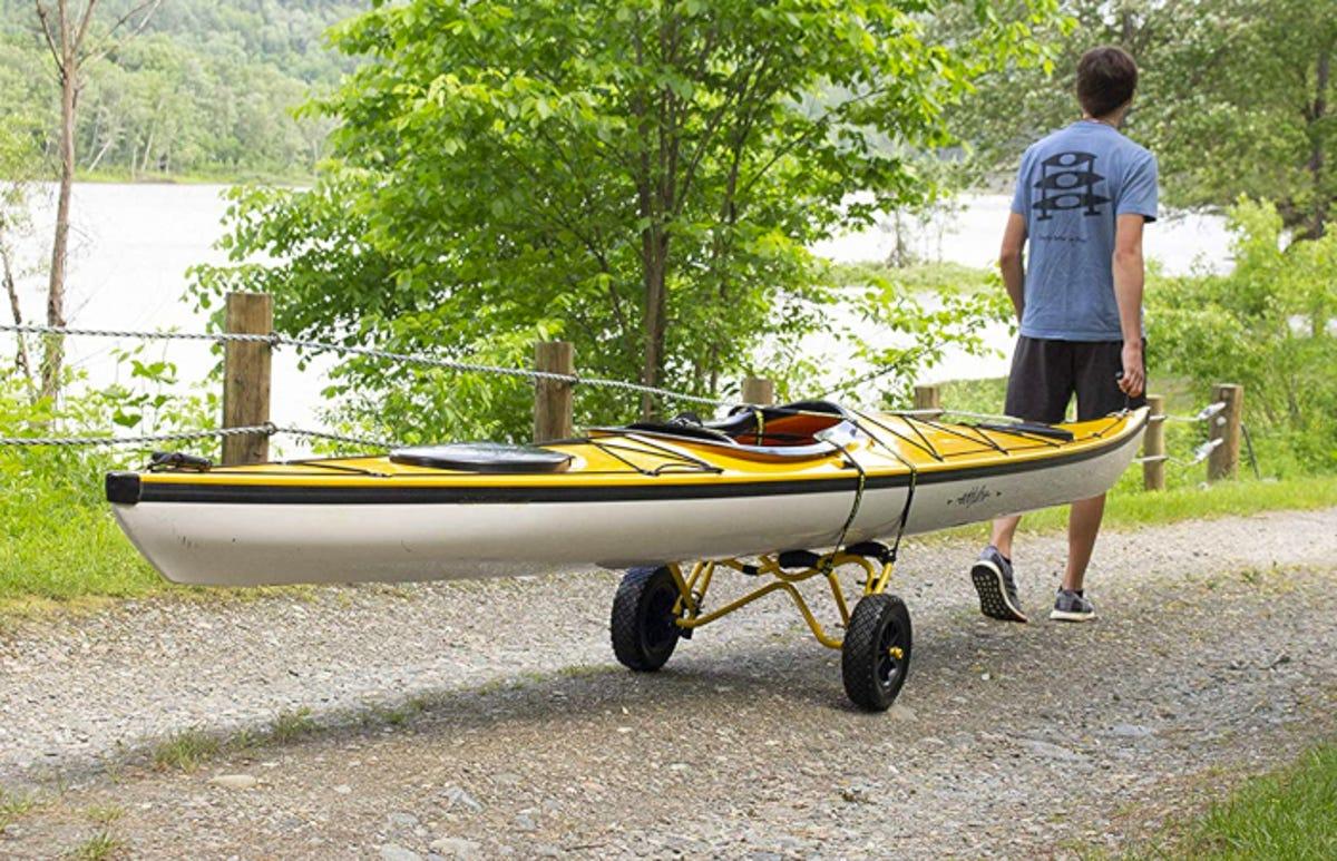 man pulling a kayak on a kayak cart down to a lake