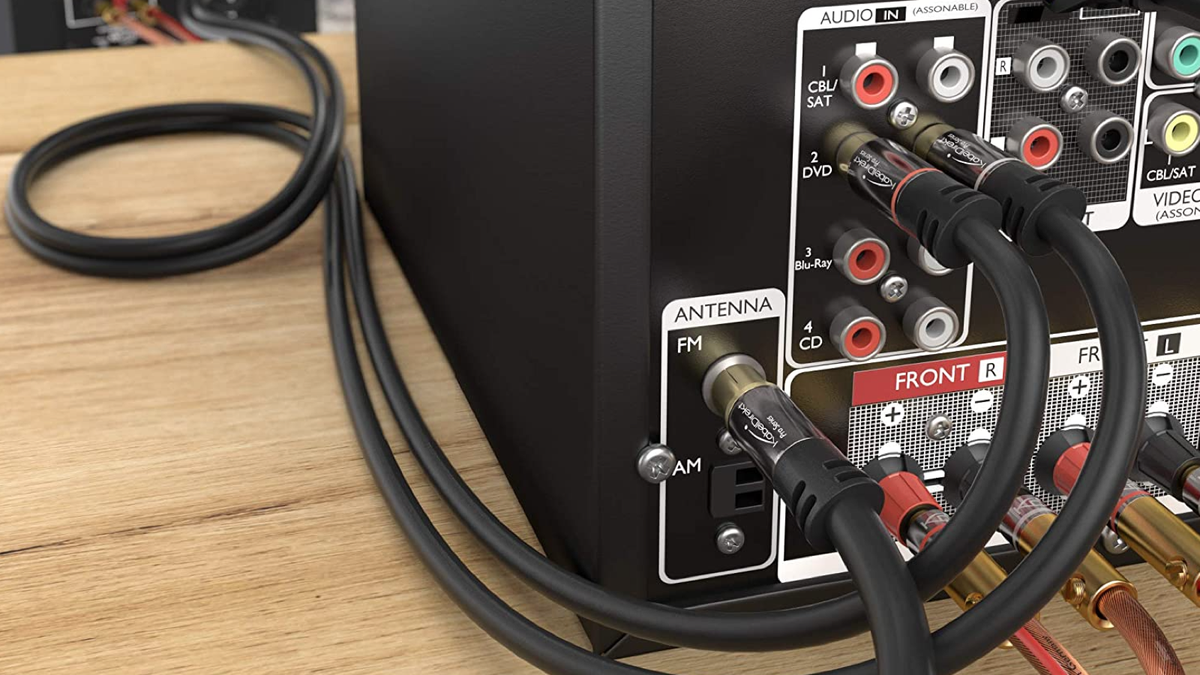 several RCA cables plugged into the back of a black TV box