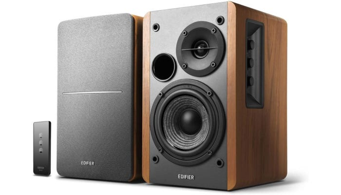 pair of black and brown studio monitors with a remote control