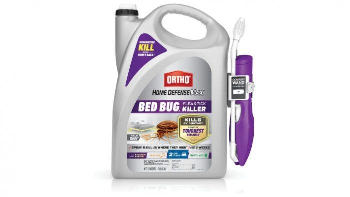 large white and purple bottle of bed bug spray with a carrying handle and extendable nozzle