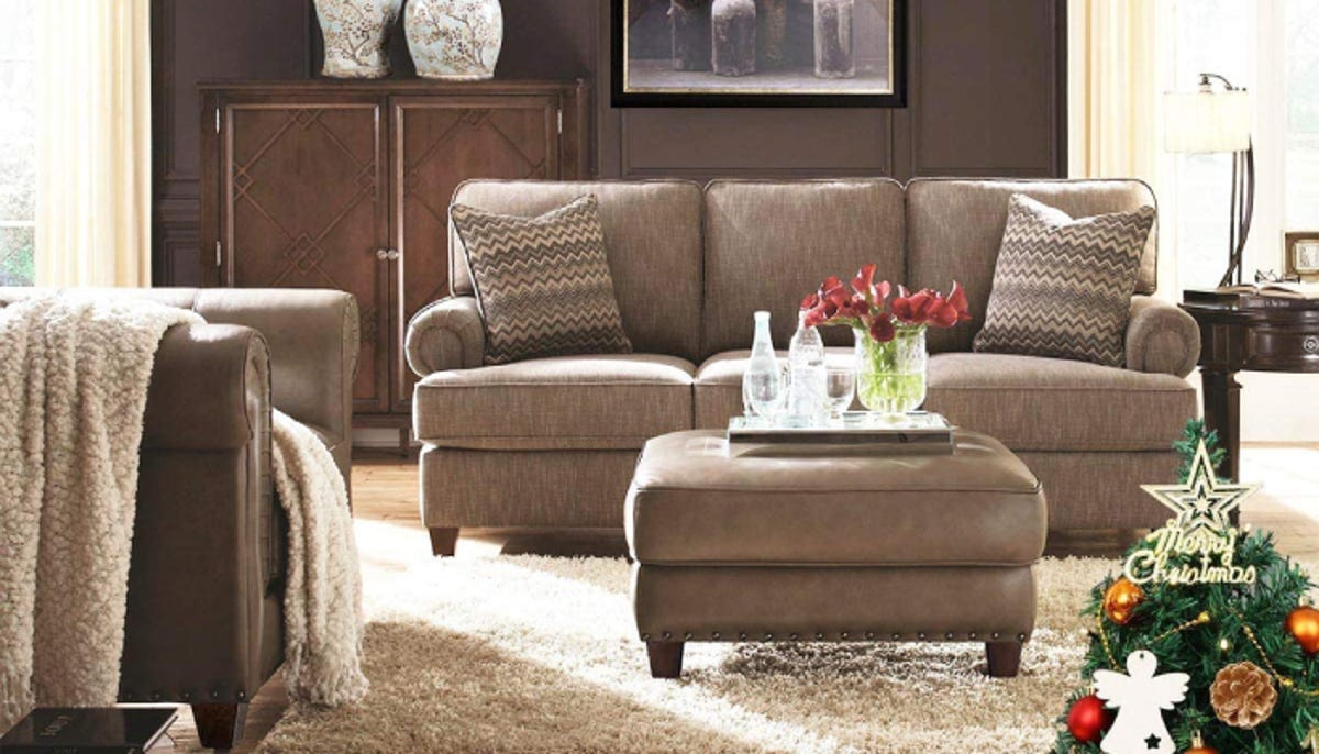 light brown couch with a matching ottoman in the middle of an old fashioned living room