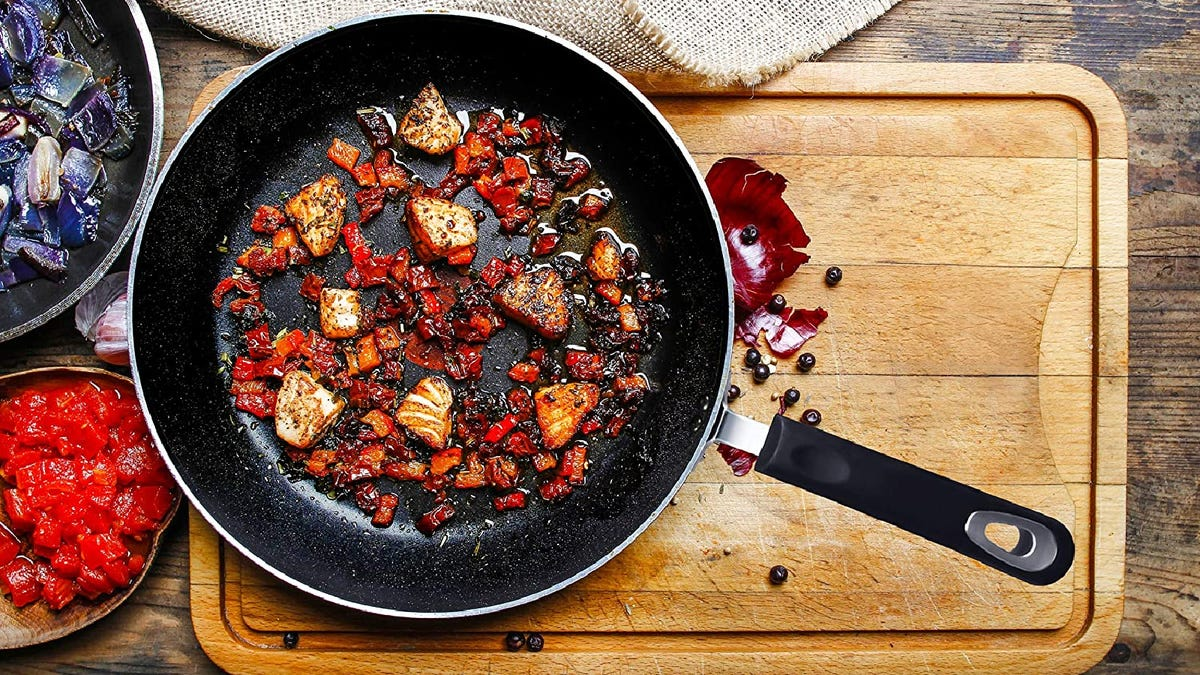 black frying pan full of cooked vegetables on top of a cutting board and wooden table