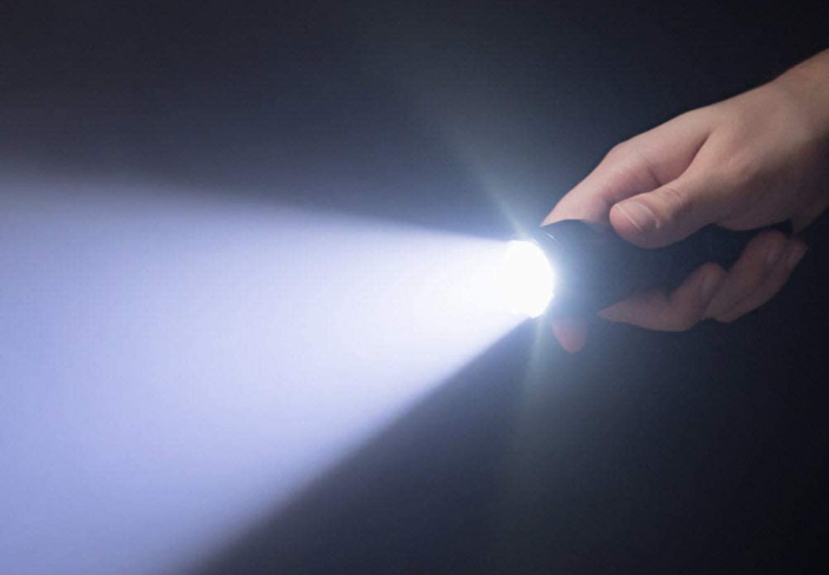 a hand shining a flashlight in the darkness