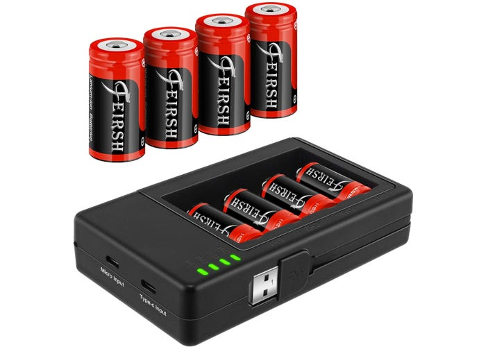 four red CR123A batteries standing and four more resting in a charger