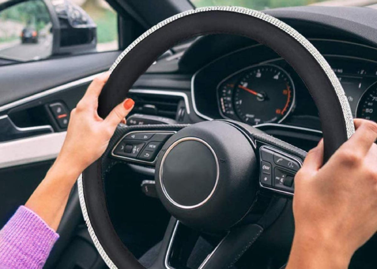 two hands on a car steering wheel that has a bedazzled cover on it