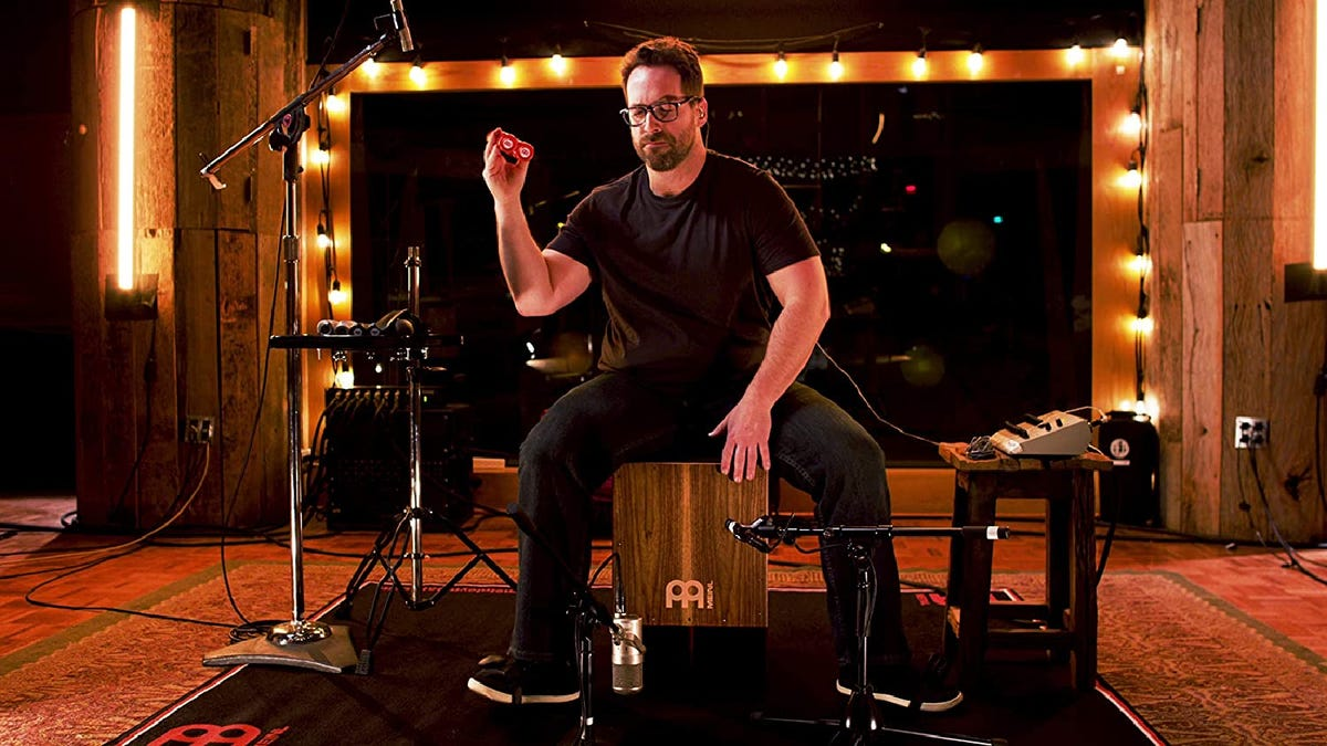 man passionately playing a Cajon drum in a studio.