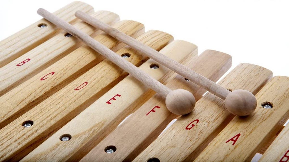 closeup of unpainted wooden xylophone keys and two mallets