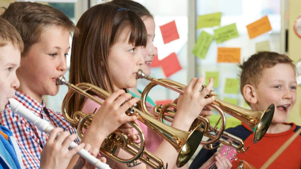 A line of young students play different instruments.
