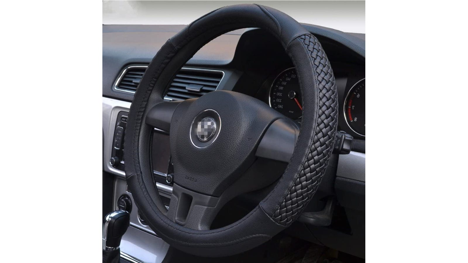 A steering wheel with a black cover that has a woven pattern on two sides.