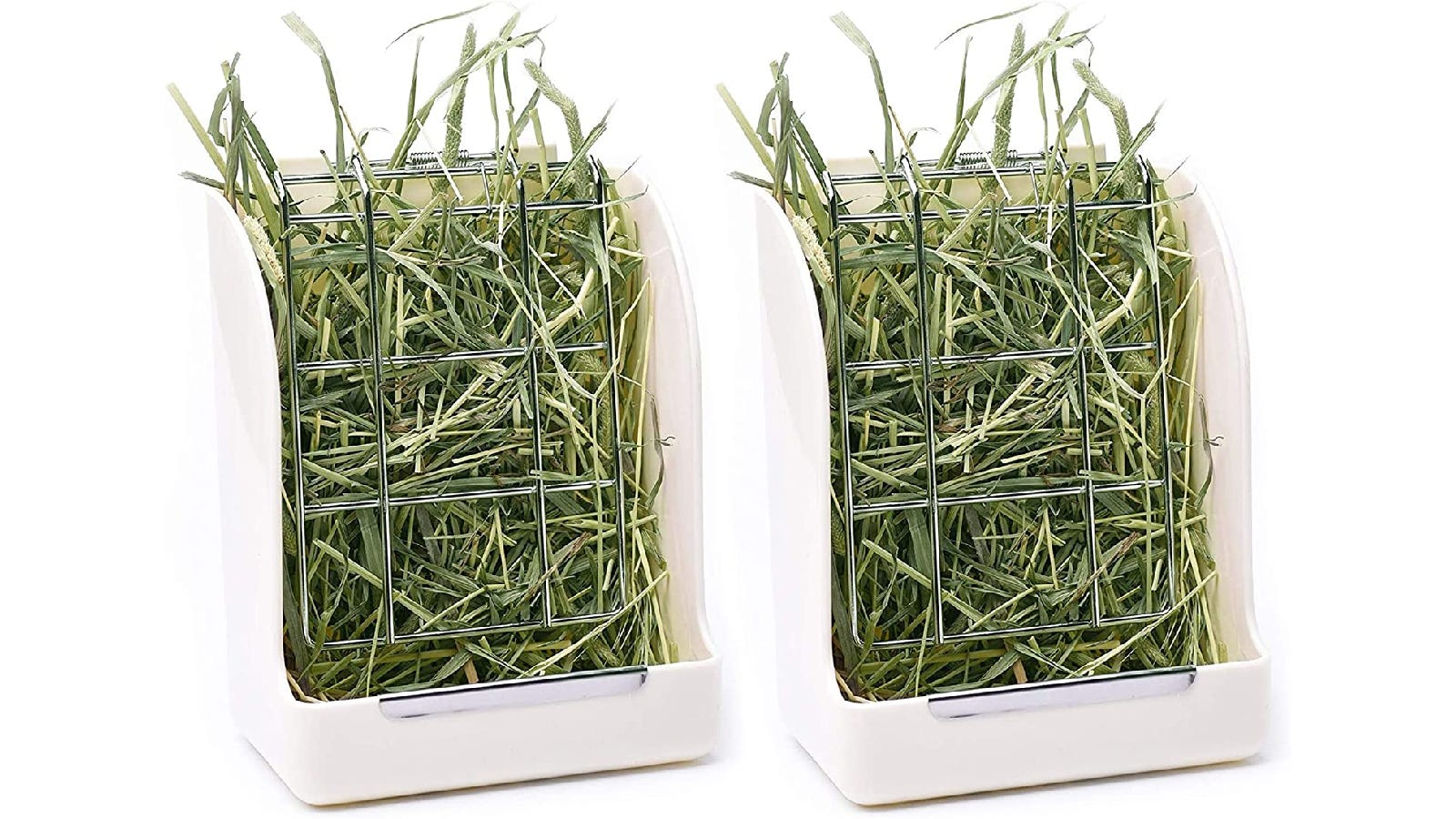 Two identical white plastic hay feeders filled with green hay.