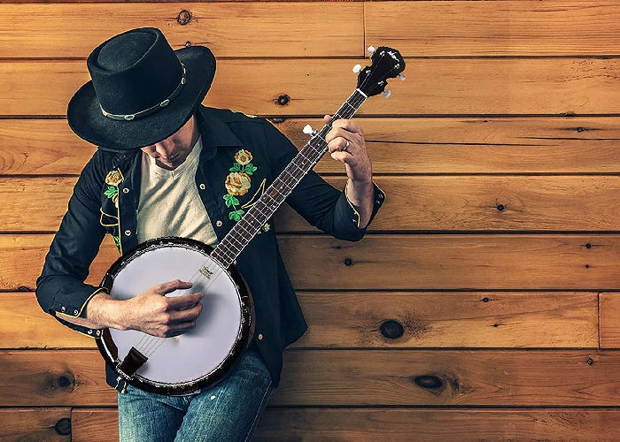 A man wearing a black hat and shirt leans against a wooden wall and plays the banjo.