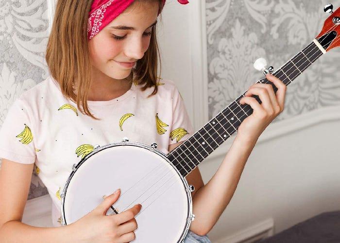 A young girl strums a tenor banjo.