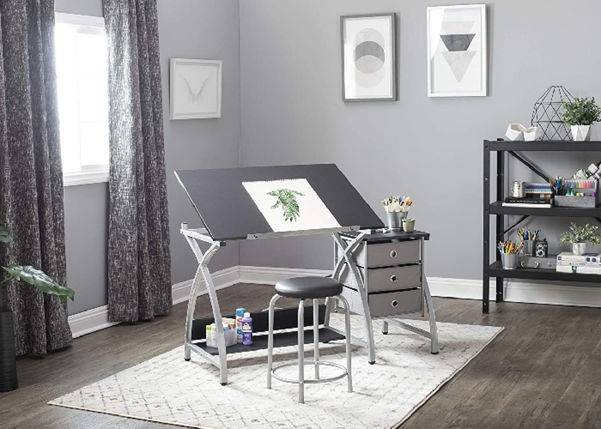 An adjustable desk with three drawers to the right and a padded stool. Stationed in a room.