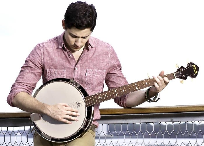 A man leans against a fence and strums the banjo.