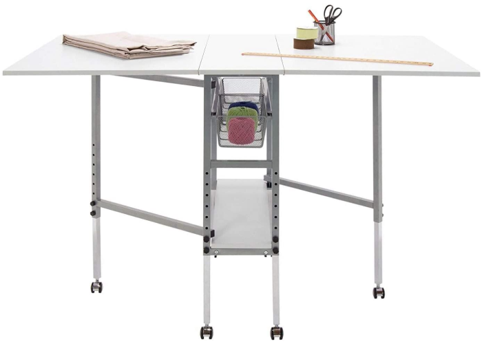 A collapsible and adjustable white craft folding table with three mesh drawers for storage in the middle.