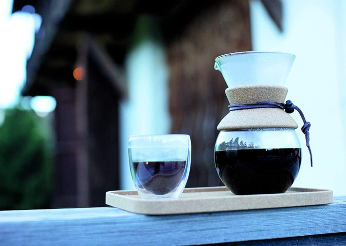 Glass pour-over coffee carafe pictured outdoors on a wooden tray with a small glass of black coffee.