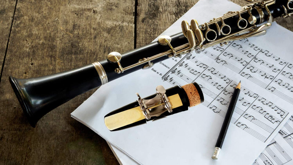 clarinet, a clarinet mouthpiece with the reed showing, a pencil, and sheets of music stacked on a wooden table
