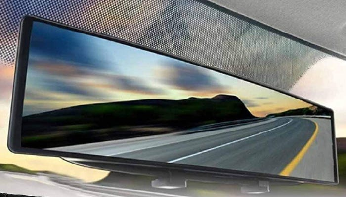 A car rearview mirror displays a view of an empty road, mountains, and blue/pink sky.