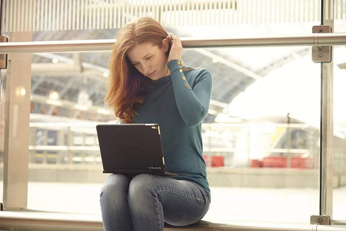 Woman sitting in front of window using an iPad in a case