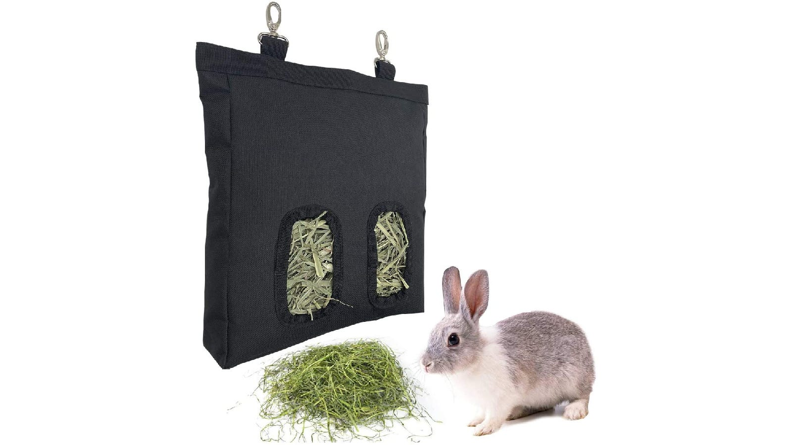 Black canvas hay feeder with hay sticking out of two circular openings. Below the bag sits a rabbit next to a pile of hay.