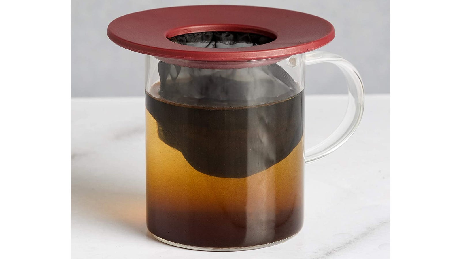 Plastic portable pour-over coffee device with an attached mesh filter placed atop a glass mug filled with coffee.