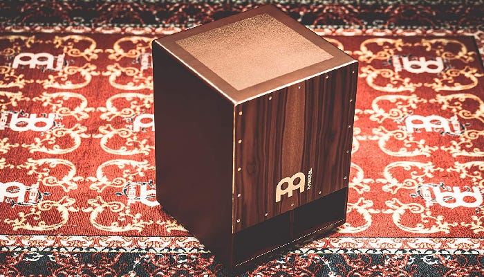 box-shaped wooden Cajon drum with two front-facing sound ports near the bottom.