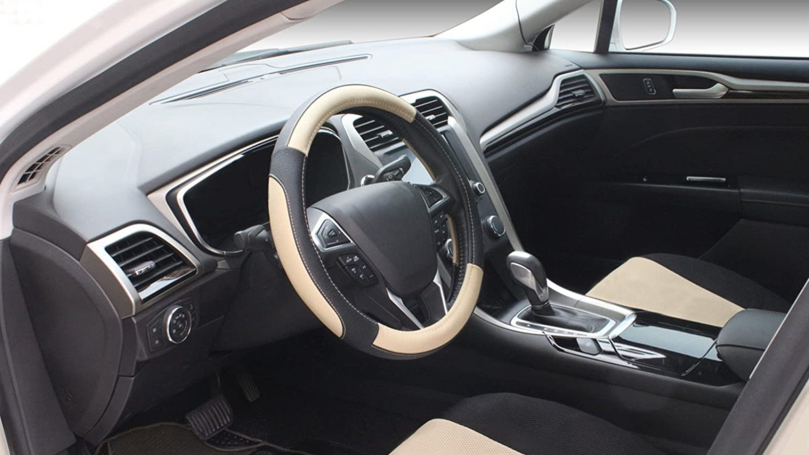 The front interior of a car and the steering wheel has a black and beige cover on it.