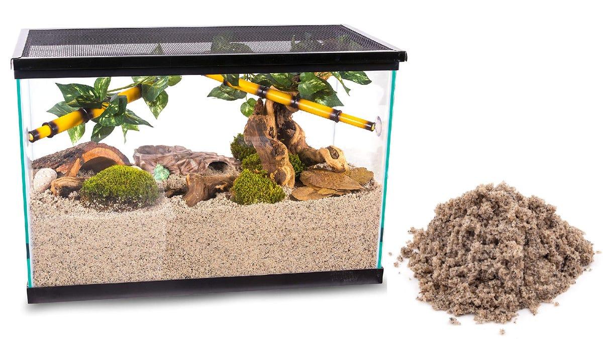 square aquarium tank placed next to a pile of beige aquarium sand