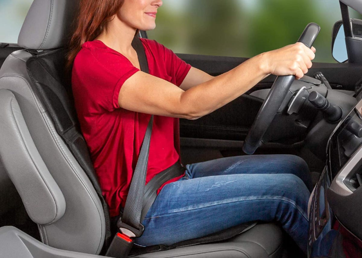 A red-haired woman in a red shirt is driving her car while sitting on a car seat cover.