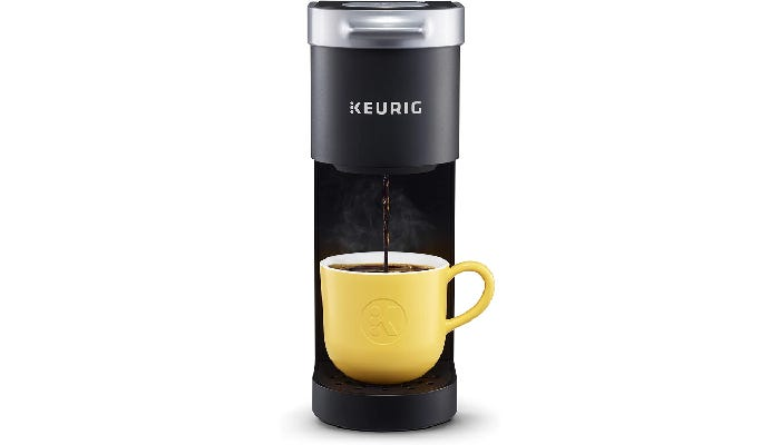 A matte black and silver coffee maker that stands just over a foot tall and less then five inches wide.