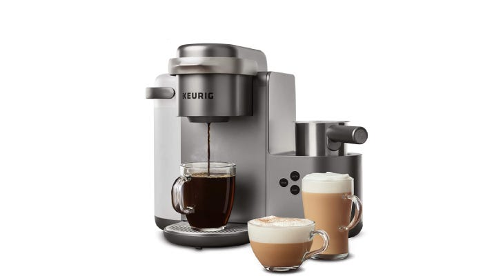 A larger, nickel-colored coffee machine that features a water tank on its left, a coffee drip at center, and a milk frother on the right.