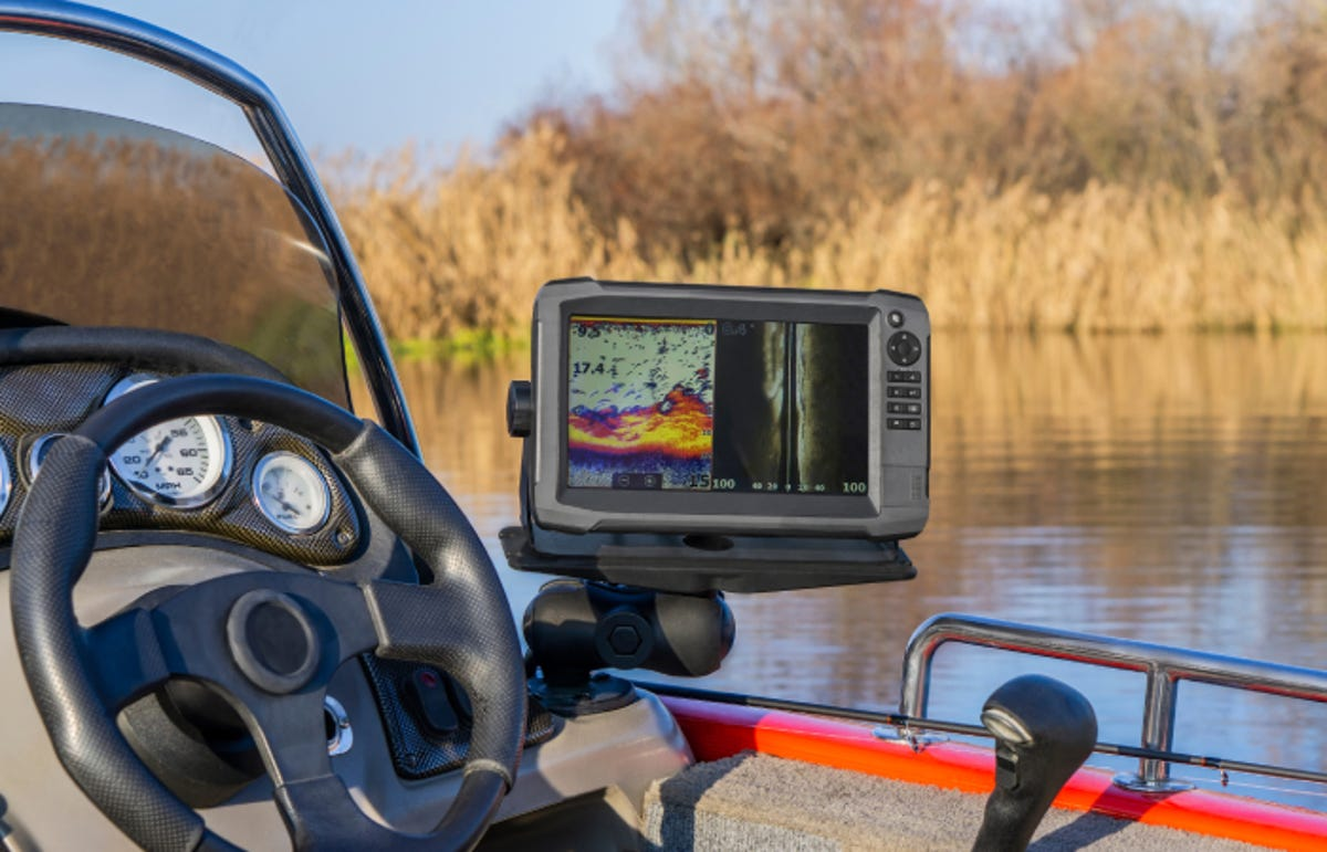 a fish-finder next to the steering wheel of a boat that's on a lake